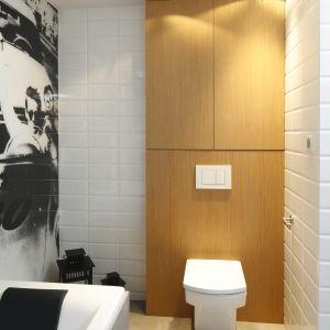 Nad sedesem znajduje się drewniana szafa. Półki w ścianie umożliwiają przechowywanie drobnych akcesoriów i kosmetyków. Naturalny dąb wizualnie ociepla loftową łazienkę. Fot. Bartosz Jarosz