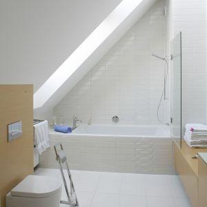 Biała łazienka pod skosami ma elementy z drewna w jasnym kolorze. Proj. Alina Grzybowska, Konstanty Jeżewski. Fot. Bartosz Jarosz