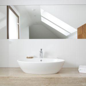 Nad elegancką umywalką znajduje się lustro, przycięte pod skos, które optycznie powiększa pomieszczenie. Światło naturalne wpuszczają dwa okna dachowe. Proj. Piotr Stanisz. Fot. Bartosz Jarosz