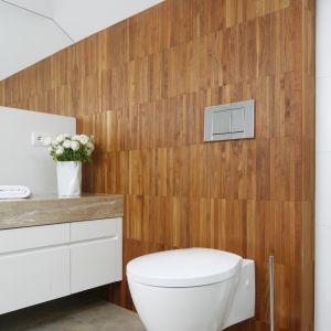 Ścianę za sedesem wykończono naturalnym drewnem – mozaiką z teaku. Na podłodze zostały ułożone jasne płytki gresowe w dużych formatach. Proj. Piotr Stanisz. Fot. Bartosz Jarosz