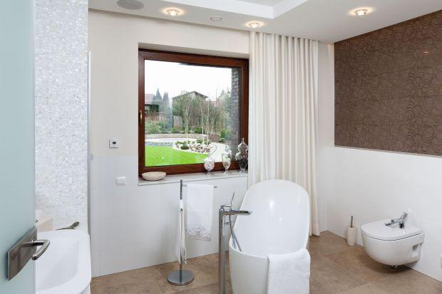 W tej łazience dominują miękkie linie i piękne detale. Wolno stojąca wanna i telewizor na ścianie wprowadzają element luksusu, a stonowane kolory zachęcają do relaksu.