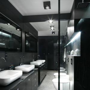 W tej nowoczesnej łazience zarówno nad lustrem, jak i w centrum sufitu zainstalowano dyskretne, punktowe oświetlenie w czarnej zabudowie. Wnękę nad wc podświetla taśma ledowa. Projekt: Maciejka Peszyńska-Drews. Fot. Bartosz Jarosz
