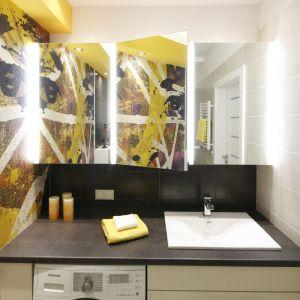 Po dwóch stronach szafki z lustrzanymi frontami zainstalowano ledowe taśmy. Dodatkowe światło zapewnia punktowe oświetlenie w żółtej zabudowie sufitu. Projekt: Monika Olejnik. Fot. Bartosz Jarosz