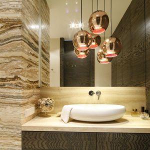 Miedziane, okrągłe klosze są efektowną dekoracją tej łazienki. Projekt: Agnieszka Ludwinowska. Fot. Bartosz Jarosz