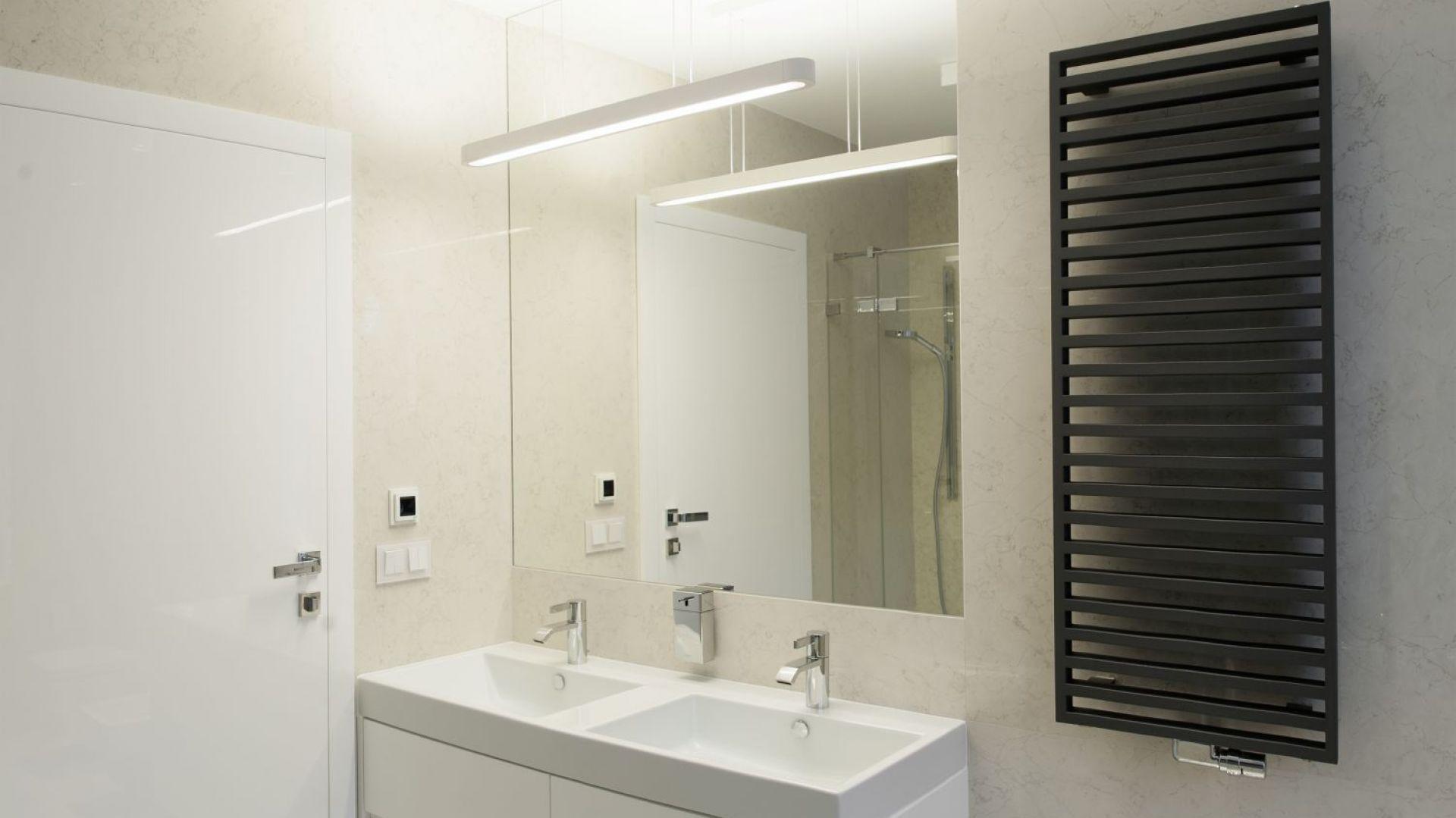 W nowoczesną aranżację łazienki idealnie wpisuje się proste, techniczne oświetlenie nad szafką umywalkową. Projekt: arch. Marta Pala-Szczerbak, Minimoo. Fot. Piotr Lipiecki