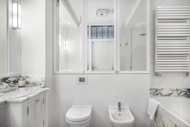 Biała łazienka w sopockim mieszkaniu została urządzona w bieli, której pazura dodają strukturalne płytki i naturalny marmur na ścianach.