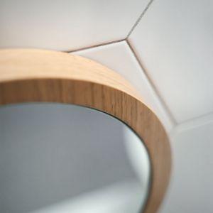 Okrągłe lustro zamknięto w drewnianą ramę. Projekt: Raca Architekci. Fot. Adam Ościłowski