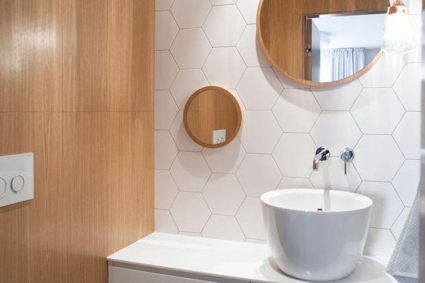 Naturalne drewno dębowe, śnieżna biel oraz modne kształty. Tak urządzono toaletę w gdańskim apartamencie.