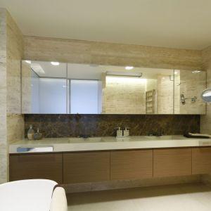 Łazienka jest bardzo przestronna, a dodatkowo powiększa ją rząd lustrzanych szafek nad blatem. Projekt: Anna Fodemska. Fot. Bartosz Jarosz