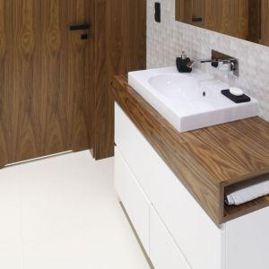 Blat w kolorze drewna harmonizującego z okleiną drzwi ma ciekawą formę - jest pusty w środku, co pozwoliło na stworzenie w nim schowka, np. na ręczniki. Projekt: Jan Sikora. Fot. Bartosz Jarosz