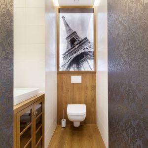 Przestrzeń wąskiej toalety optycznie skrócono i poszerzono wykańczając ściany ciemną, zdobną tapetą przy wejściu do pomieszczenia, i białymi płytkami w jego głębi. Projekt: Arte Architekci. Zdjęcia: Arte Architekci