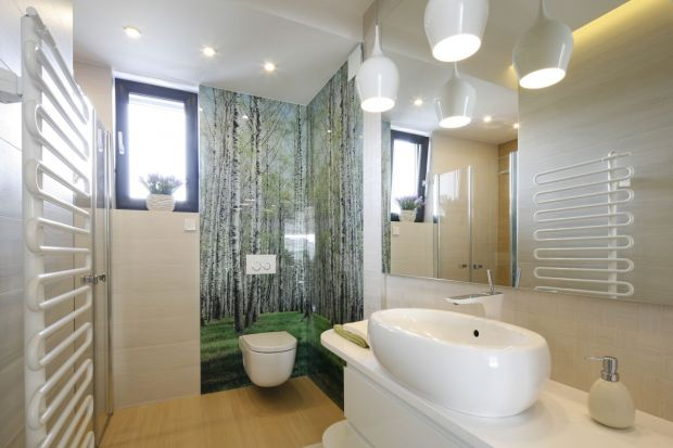 Naturę do przestrzeni łazienki możemy wprowadzić na wiele sposobów. Jednym z nich jest udekorowanie ściany motywem leśnym.