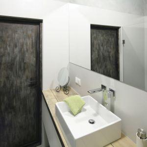 Małą łazienkę optycznie powiększa ogromne lustro zamontowane nad umywalką. Projekt: Małgorzata Chabzda. Fot. Bartosz Jarosz