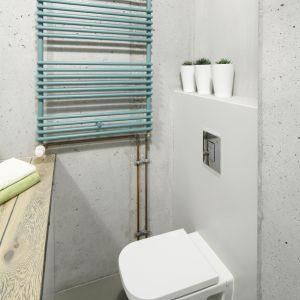 Kroplę koloru do łazienki w stylu loft wprowadzono m.in. za pomocą turkusowego grzejnika. Projekt: Małgorzata Chabzda. Fot. Bartosz Jarosz