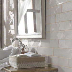 """Ścianę w strefie umywalki wykończono połyskującymi płytkami ceramicznymi Alhambra Poitiers Ecru Unique o ciekawej, """"nierównej"""" formie z kolekcji FS. Fot. Peronda"""