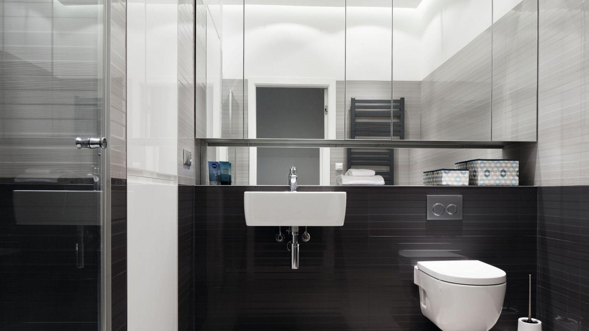 Wysoka pod sam sufit górna zabudowa z lustrzanymi frontami powiększa optycznie łazienkę. Projekt: Anna Maria Sokołowska. Fot. Bartosz Jarosz