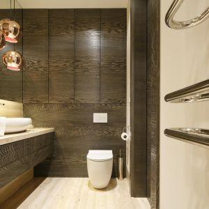 Górne szafki pod sam sufit wykończono eleganckim fornirem, który buduje w łazience przytylną, ciepłą atmosferę. Projekt: Agnieszka Ludwinowska. Fot. Bartosz Jarosz