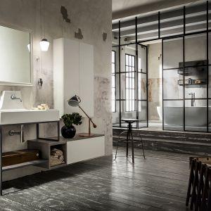 Aranżacja łazienki w stylu industrialnym zaproponowana przez firmę Cerasa, z kolekcją mebli Urban Play. Białe matowe fronty zestawiono z metalowym szkieletem. Ścianę pokrywa obdrapany tynk, a na podłodze widnieje postarzana deska. Charakterystycznym akcentem jest laboratoryjny stołek. Fot. Cerana
