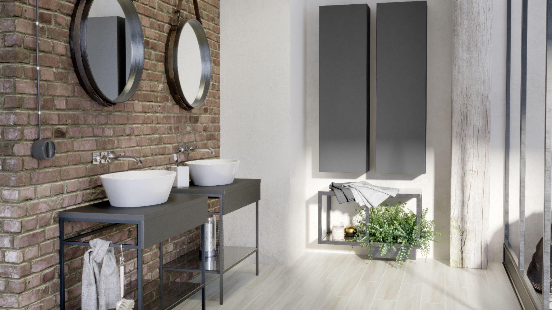 Łazienka w stylu industrialnym według marki Opoczno. Kolekcja łazienkowa Splendour z meblami w matowym, grafitowym kolorze wspartych na metalowych nóżkach. Świetnie prezentują się na tle czerwonej cegły. Fot. Opoczno