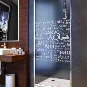 Uchylne drzwi wnękowe Nigra marki Aquaform z typograficznym dekorem na szkle. Fot. Aquaform