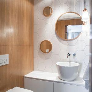 Aranżacja białej łazienki ocieplonej kolorami drewna. Proj. Raca Architekci. Fot. Adam Ościłowski