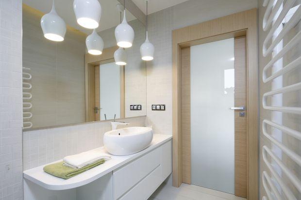 Biała łazienka nie musi być sterylna i chłodna w odbiorze. Wystarczy ocieplić ją odrobiną kolorów drewna.