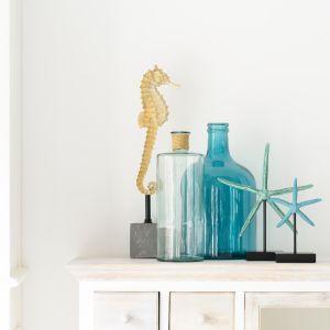 W łazience w stylu marynistycznym świetne sprawdzą się wszelkie dekoracja nawiązujące formą do zwierząt morskich. Z kolei puste butelki sprawią, że zechcemy włożyć do nich list i wyrzucić do morza. Fot. House&More