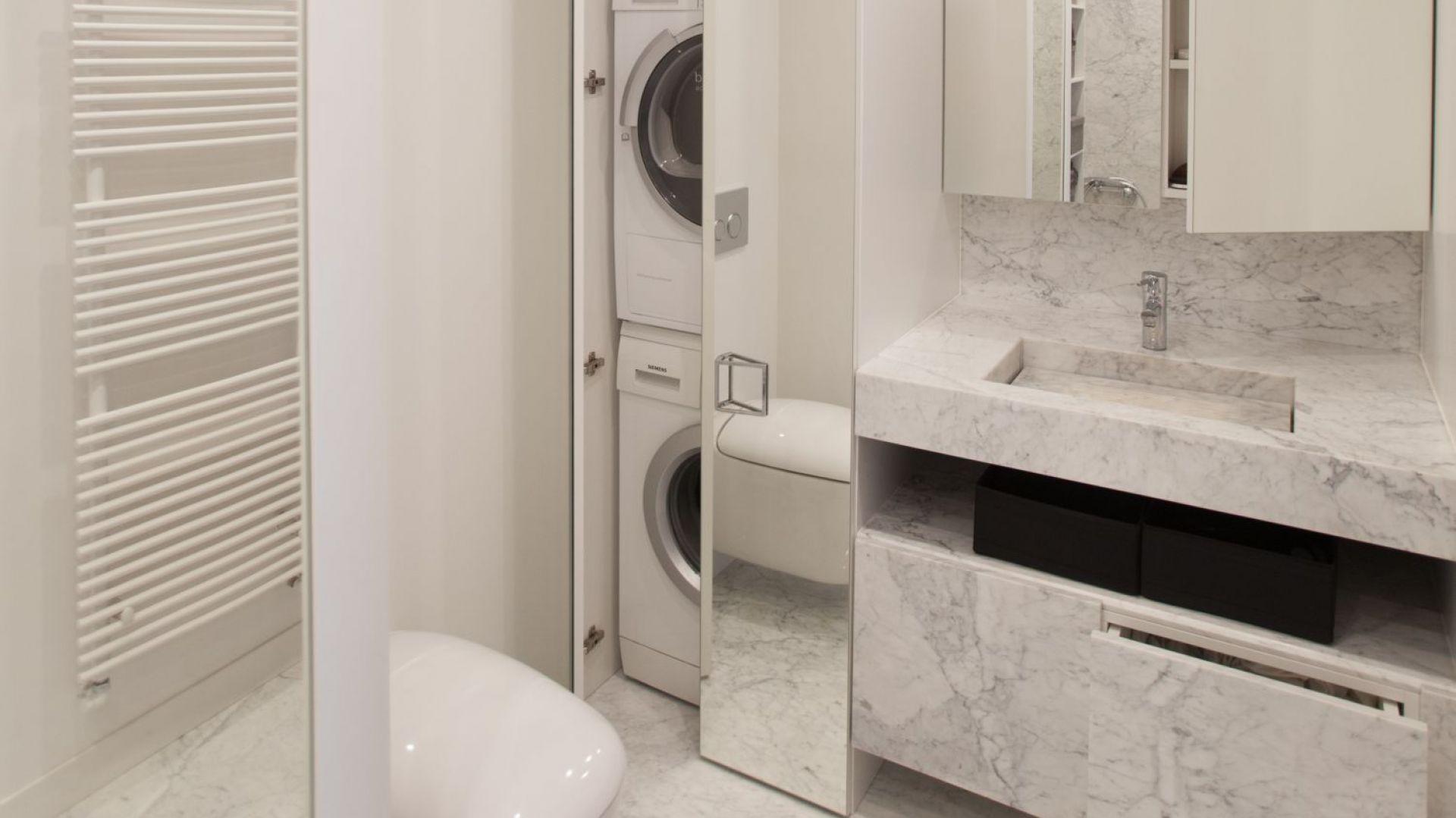 Wysoki słupek pomieścił nie tylko pralkę, ale i suszarkę. Lustrzany front powiększa optycznie łazienkę. Proj. Studio Prostych Form. Fot. Studio Prostych Form