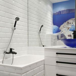Bardzo małą łazienkę urządzono na biało. Dodatkowo optycznie powiększa ją duże lustro i fototapeta z panoramą Santorini. Proj. Ewa Para. Fot. Bartosz Jarosz