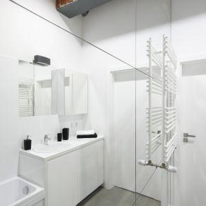 Mała biała łazienka jest również bardzo wąska. Optycznie poszerza ją jednak lustrzana ściana. Proj. Nowa Papiernia. Fot. Bartosz Jarosz