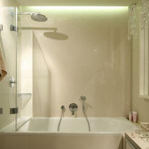 Duże lustro, jasna kolorystyka i wanna z parawanem - te rozwiązania zastosowano w tej małej łazience. Proj. Małgorzata Borzyszkowska. Fot. Bartosz Jarosz