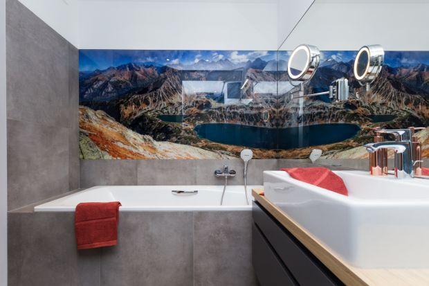 Utrzymana w biało-szarej tonacji łazienka ma oryginalny i dynamiczny wystrój. Klimat buduje tu tapeta z malowniczym górskim krajobrazem. To on nie tylko zachęca do relaksu, ale też mobilizuje do codziennych aktywności.