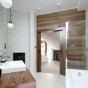 Nowoczesna łazienka z płytkami ceramicznymi imitującymi drewniana deską wokół wejścia i futurystycznymi kaflami 3D na pozostałych ścianach. Proj. Jan Sikora. Fot. Bartosz Jarosz