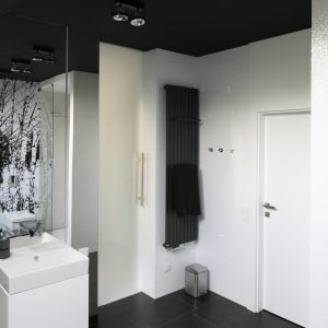 Wyeksponowany na tle białej ściany czarny grzejnik wyposażono w dwa czarne relingi na ręczniki. Proj. łazienki: Dominik Respondek. Fot. Bartosz Jarosz