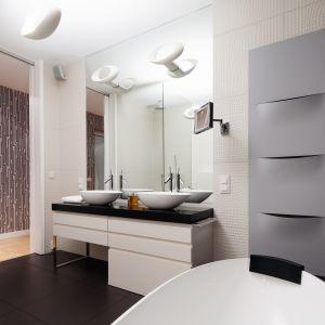 Efektowny grzejnik wpisuje się w futurystyczną aranżację łazienki swoją lekko wygiętą formą z intrygującymi otworami. Proj. łazienki: Justyna Smolec. Fot. Bartosz Jarosz