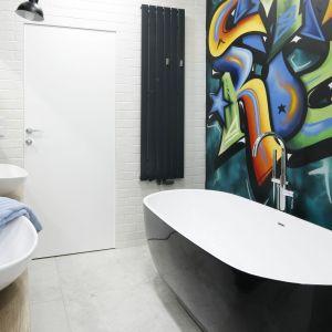 Grzejnik łazienkowy kolorystycznie współgra z ciemnym wykończeniem wanny, a jego forma - z nowoczesną aranżacją łazienki. Został również wyposażony w praktyczne wieszaki na ręczniki. Proj. łazienki: Dariusz Grabowski. Fot. Bartosz Jarosz