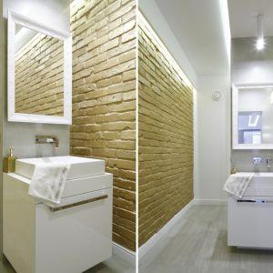 Pomalowana na złoto cegła wieńczy ścianę w łazience. Proj. Dominik Respondek. Fot. Bartosz Jarosz