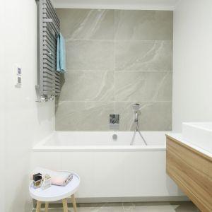 Podłoga w łazience harmonizuje ze ścianą nad wanną - jedną i drugą zdobi gres imitujący kamień. Proj. Przemysław Kuśmierek. Fot. Bartosz Jarosz