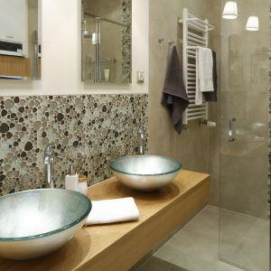 Szklane umywalki w zielonkawym kolorze wprowadzają barwny akcent do łazienki urządzonej w stonowanej stylistyce. Proj. Właściciele. Fot. Bartosz Jarosz