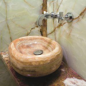 Na tle wykończonej kamieniem ściany stanęła umywalka wykonana z prawdziwego onyksu. Proj. Kinga Śliwa. Fot. Bartosz Jarosz