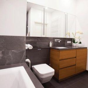 Drewno nawet na niewielkiej powierzchni może radykalnie zmienić atmosferę wnętrza. Dowodem na to jest ta łazienka. Gdyby nie było szafki  podumywalkowej z drewna iroko, panowałby w niej surowy klimat. Fot. Pracownia Architektoniczna MGN