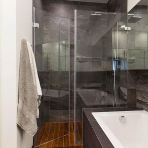 Drewniana podłoga rzadko bywa kładziona w kabinie prysznicowej. Tutaj się na to odważono. Wybrano zaolejowane deski iroko i położono je tak, jak na jachtach, tzw. szczeliny między nimi wypełniono elastomerem, elastycznym tworzywem, które nie pęka. Woda więc nie wnika pod drewno. Fot. Pracownia Architektoniczna MGN