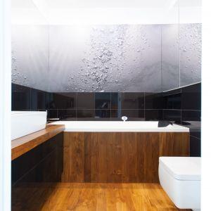 Po drewnianej podłodze można chodzić boso i nie zmarznąć. Bardzo ważny również jest jej luksusowy i dekoracyjny wygląd. W tej łazience użyto desek tekowych – o głębokiej barwie i pięknym rysunku słojów – których uroda uwydatniła się w pełni po zaolejowaniu. Z tego samego materiału są też blaty i obudowa wanny.  Fot. Pracownia Architektoniczna MGN
