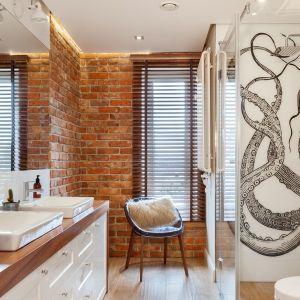 Ściana w łazience wykończona czerwoną cegła. W strefie prysznica - grafika z maskami ośmiornicy. Proj. Arte Architekci. Fot. Arte Architekci
