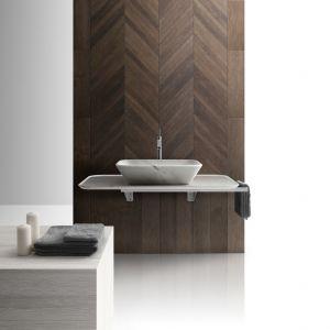 Płytki jak drewno z kolekcji Hana ułożone w klasyczną jodełkę stanowią przewrotną dekorację ściany w strefie umywalki. Fot. Kreoo