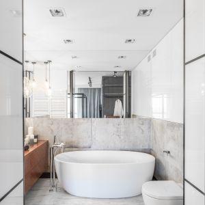 Wielkoformatowa tafla lustra nad wanną i w strefie umywalki optycznie powiększa wnętrze dodając mu głębi. Proj. Decoroom. Fot. Pion Poziom