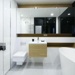 Dyskretna wnęka w strefie prysznica pełni rolę półeczki, a wnęki w strefie umywalki wykończone fornirem, ocieplają wizualnie łazienkę i dodają dynamiki aranżacji. Proj. Monika i Adam Bronikowscy. Fot. Bartosz Jarosz
