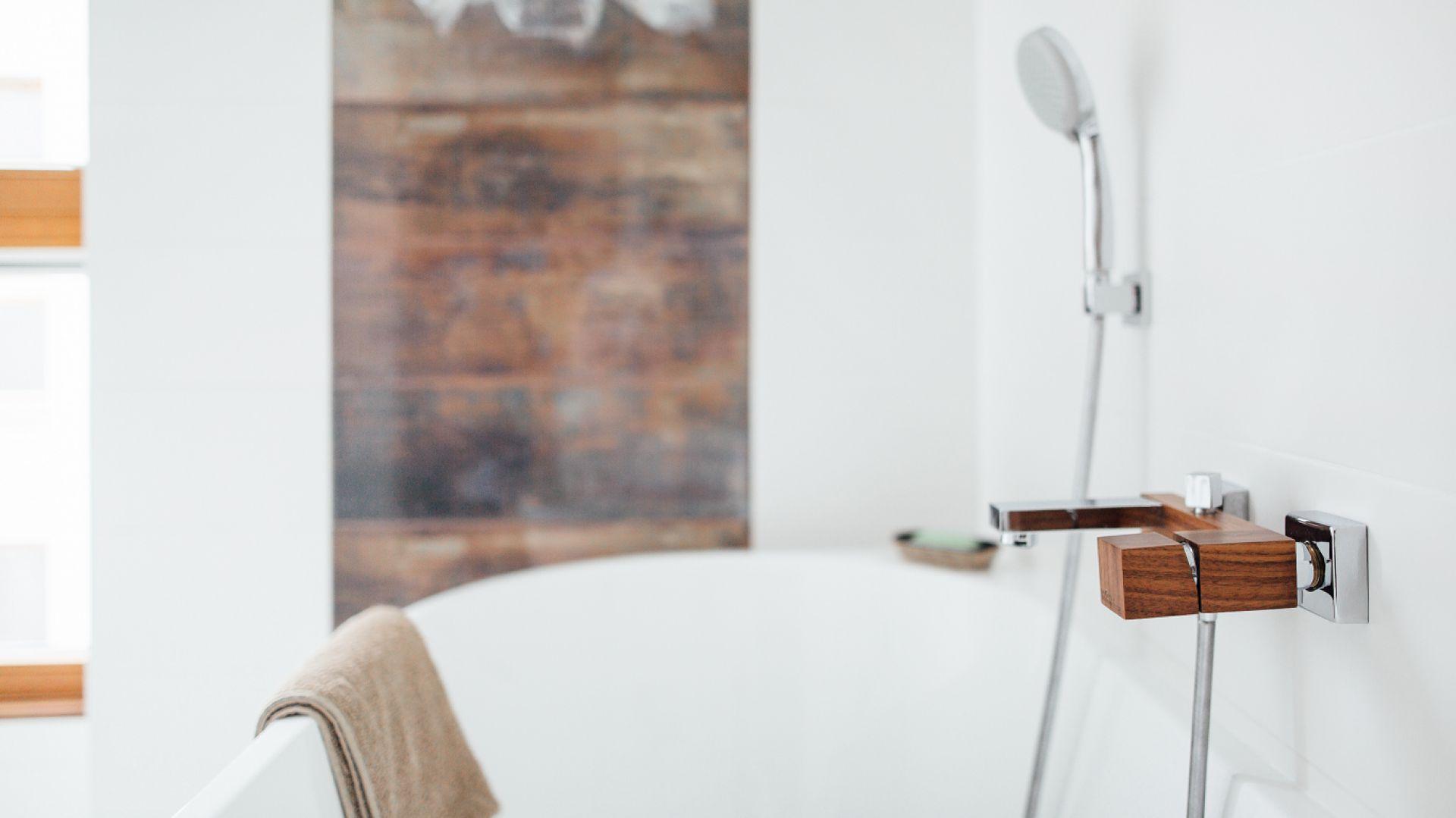 Pomysłowym i oryginalnym sposobem na wprowadzenie do łazienki drewnianego detalu jest... armatura łazienkowa. Na zdjęciu bateria wannowa wykończona naturalnym fornirem z oferty firmy Green Home Design. Fot. Green Home Design