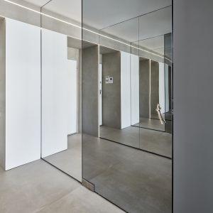 Lustrzane drzwi do sypialni mają wyjątkową ukrytą klamkę, którą jest sznurek z supełkiem. Z tego pomieszczenia mamy od razu dostęp do łazienki, do której prowadzą nas znowu LED-owe pasy. Fot. 81.WAW.PL