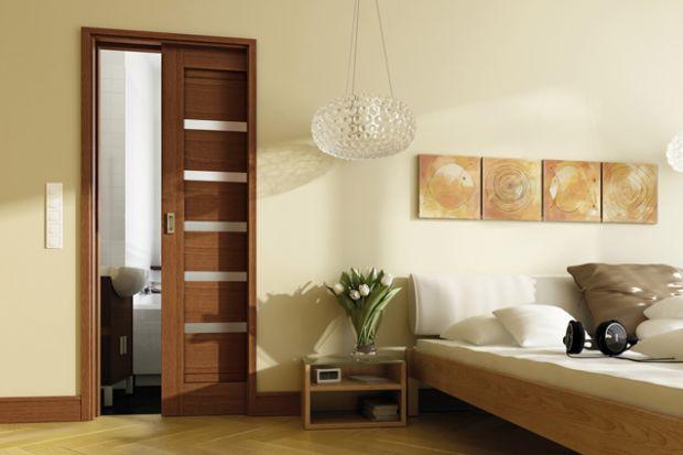 W nowych mieszkaniach i domach bardzo popularne stało się urządzanie łazienki obok sypialni. Granicę pomiędzy tymi dwoma pomieszczeniami warto zaznaczyć montując drzwi przesuwne.